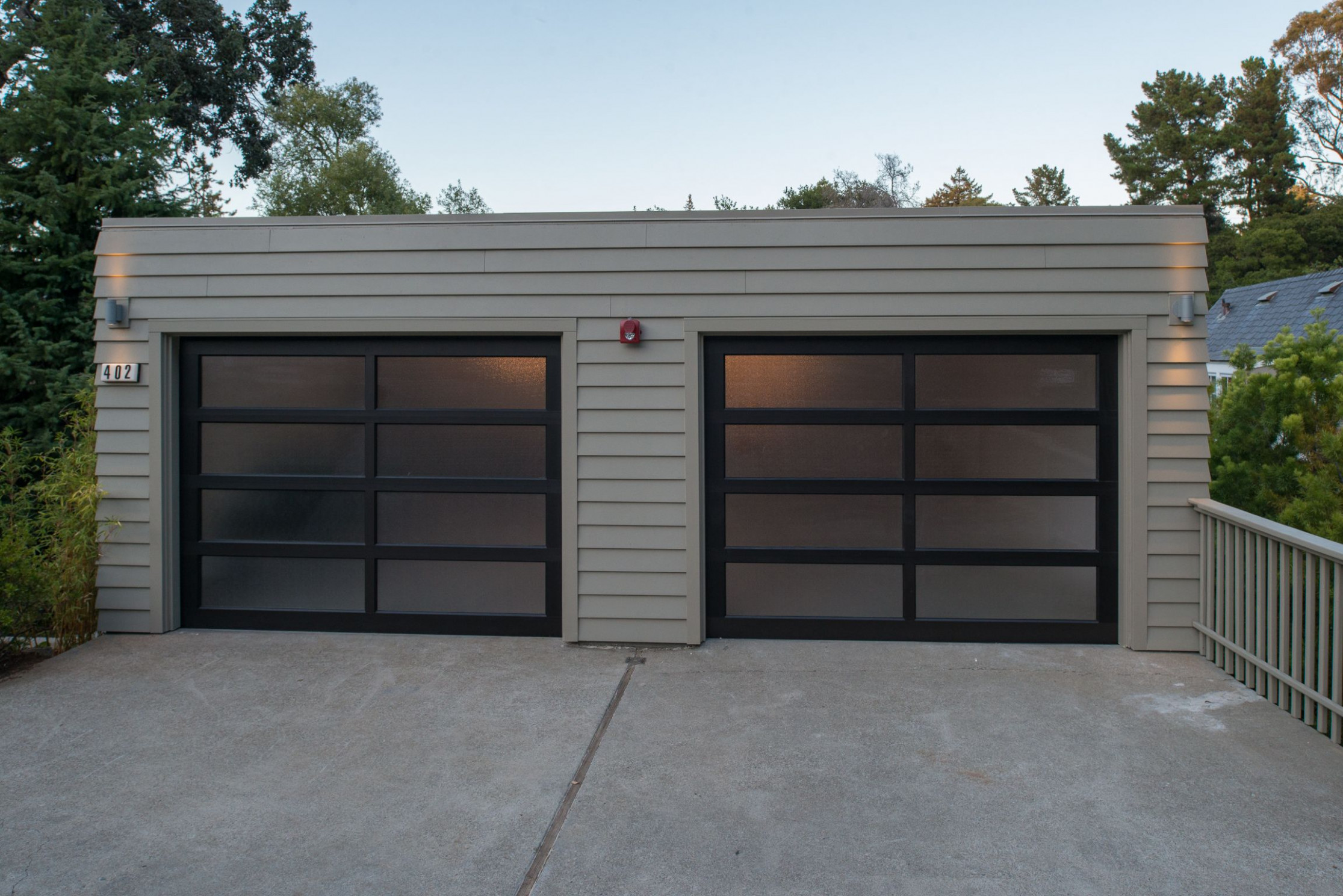 A Contemporary Garage With Beige Siding And A Black Framed ..